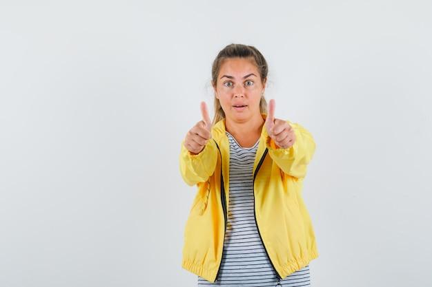 Donna bionda che mostra i pollici in su con entrambe le mani in bomber giallo e camicia a righe e sembra carina