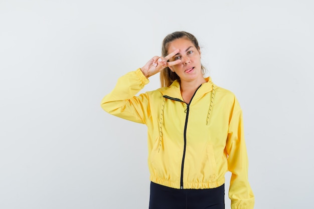 Donna bionda che mostra il segno di v sull'occhio mentre sporge la lingua in bomber giallo e pantaloni neri e sembra seria