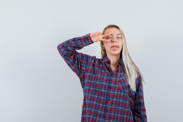 目の上にvサインを示し、チェックのシャツに舌を突き出して魅力的に見える金髪の女性、正面図。