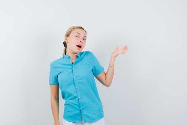 Donna bionda che mostra gesto di benvenuto in camicetta blu e sembra allegra