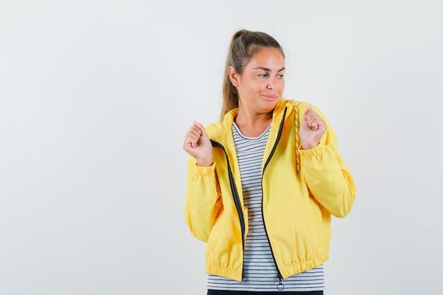 黄色のボンバージャケットとストライプのシャツで勝者のジェスチャーを示し、幸せそうに見える金髪の女性