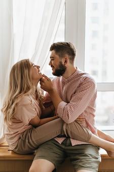 金髪の女性が彼氏に座って笑う。男は愛する人の優しそうな顔で撫でる。窓に対するカップルの肖像画。