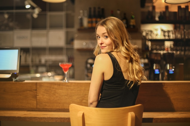 Blonde woman sitting at a bar counter