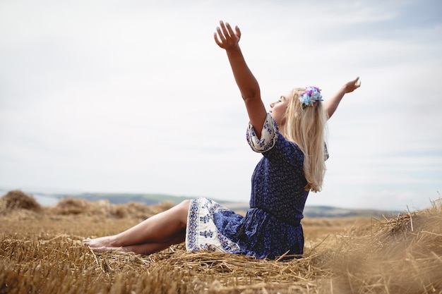 Blonde woman sitting in field with her arms raised