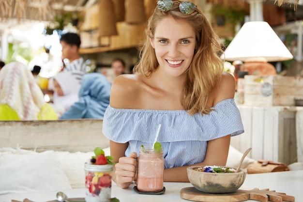 Блондинка женщина сидит в кафе