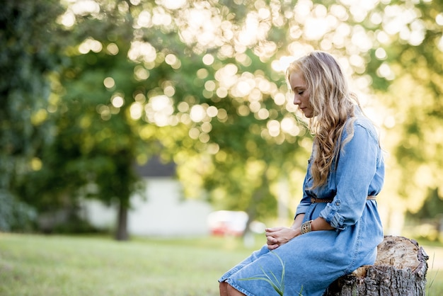 Blonde woman sitting on a tree stump and praying in a garden under sunlight