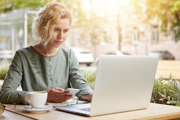 Блондинка женщина сидит с ноутбуком в кафе
