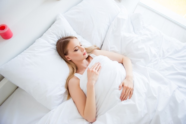 Blonde woman sleeping in her bed