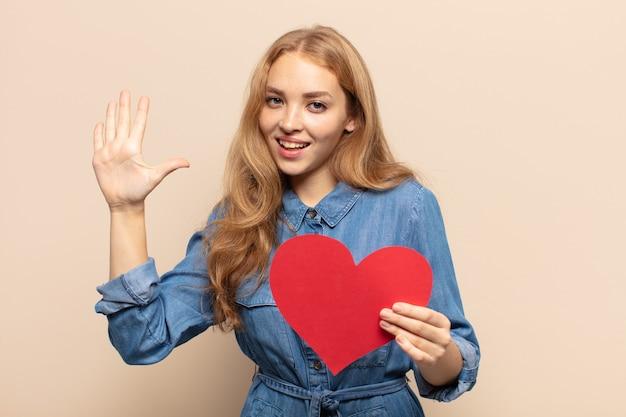 Блондинка улыбается и выглядит дружелюбно, показывает номер пять или пятое с рукой вперед, отсчитывая