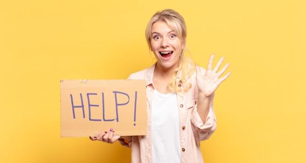 Светловолосая женщина улыбается и выглядит дружелюбно, показывает пятый или пятый номер рукой вперед и ведет обратный отсчет