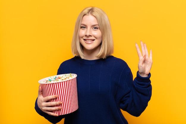 Блондинка улыбается и выглядит дружелюбно, показывает номер четыре или четвертый с рукой вперед, отсчитывая