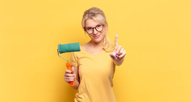 금발의 여자가 웃고 친절하게 보이고, 앞으로 손으로 넘버 원 또는 첫 번째 표시, 카운트 다운