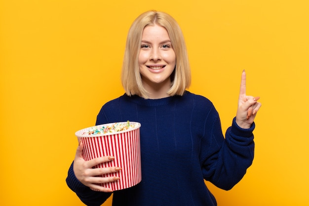 笑顔でフレンドリーに見える金髪の女性、前に手を前に、カウントダウンでナンバーワンまたは最初を示しています