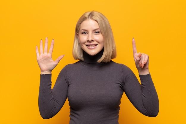 Блондинка улыбается и выглядит дружелюбно, показывает номер шесть или шестой рукой вперед, отсчитывая
