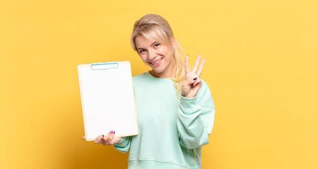 Блондинка улыбается и смотрит дружелюбно, показывает номер три или треть рукой вперед, отсчитывая