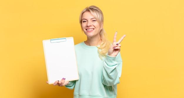 Блондинка улыбается и выглядит дружелюбно, показывает номер два или секунду рукой вперед, отсчитывая