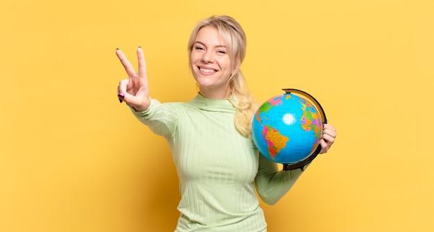 금발의 여인이 웃고 행복하고 평온하고 긍정적 인 찾고 한 손으로 승리 또는 평화를 몸짓으로 나타냅니다.