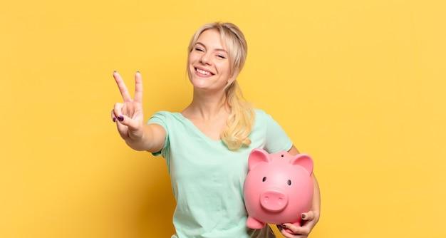 금발의 여인이 웃고 행복하고 평온하고 긍정적이며 한 손으로 승리 또는 평화 몸짓