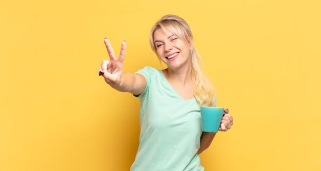 笑顔で幸せそうに見える金髪の女性、のんきで前向きで、片手で勝利や平和を身振りで示す