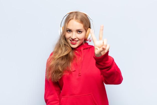 Блондинка улыбается и выглядит счастливой, беззаботной и позитивной, жестикулируя победу или мир одной рукой