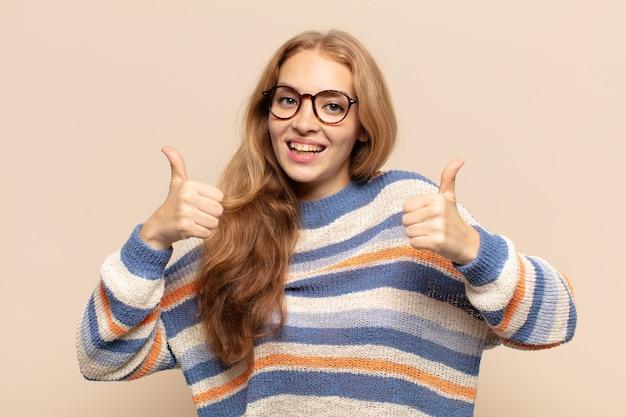 두 엄지 손가락으로 광범위하게 행복하고 긍정적이며 자신감 있고 성공적인 모습으로 웃는 금발의 여자