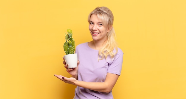 Blonde woman smiling cheerfully, feeling happy and showing a concept in copy space with palm of hand