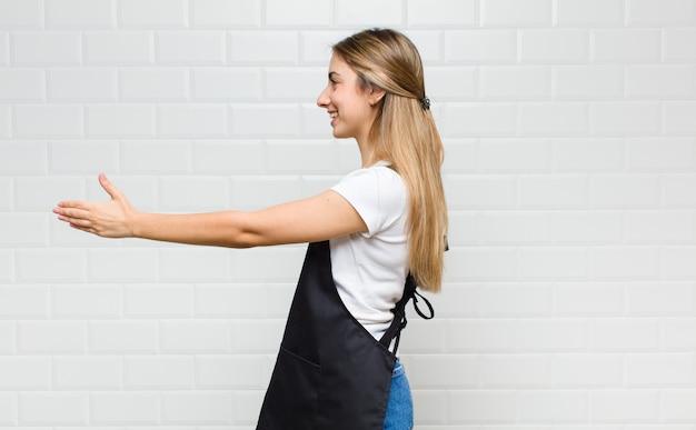 Блондинка улыбается, приветствует вас и предлагает пожать руку, чтобы закрыть успешную сделку, концепция сотрудничества