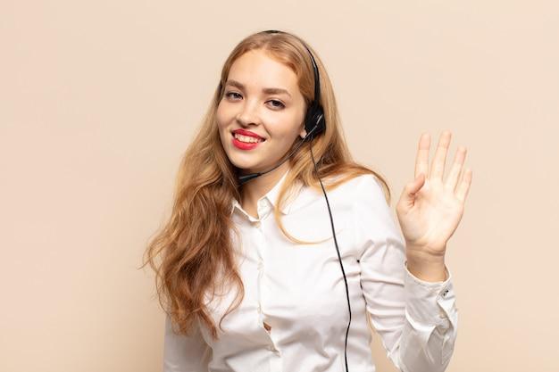 행복하고 유쾌하게 웃고, 손을 흔들며, 환영하고 인사하거나, 작별 인사를하는 금발의 여인
