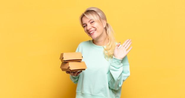 幸せにそして元気に笑って、手を振って、あなたを歓迎して挨拶するか、さようならを言うブロンドの女性