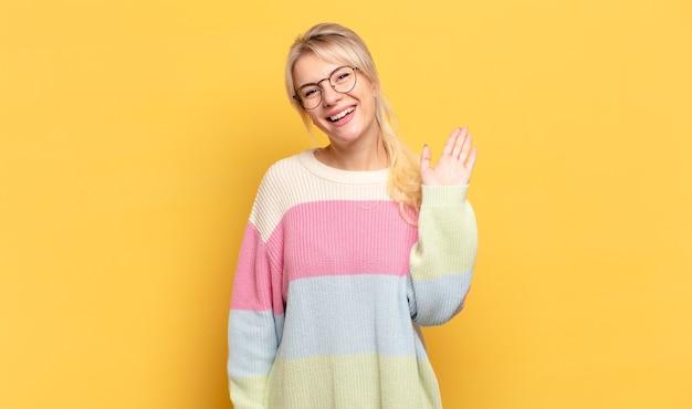 Блондинка счастливо и весело улыбается, машет рукой, приветствует и приветствует вас или прощается