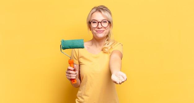 Блондинка счастливо улыбается с дружелюбным, уверенным, позитивным взглядом, предлагая и показывая объект или концепцию