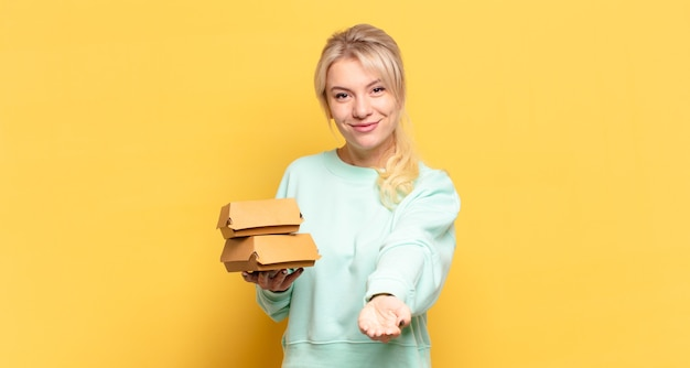 Blonde woman smiling happily with friendly, confident, positive look, offering and showing an object or concept