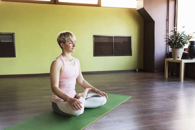 A blonde woman in sportswear practicing yoga is engaged in meditation in the lotus position sitting on a mat in the studio
