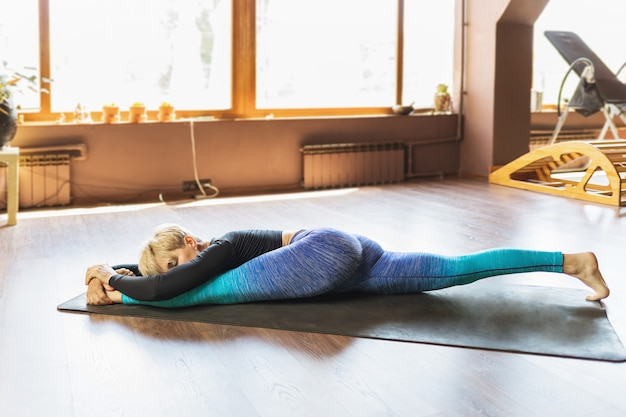 A blonde woman in sportswear practicing yoga performs hanumanasana exercise on a mat