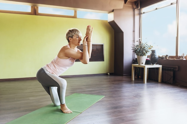 Blonde woman in sportswear, practicing yoga, standing on a mat in the studio, performs garudasana exercise, eagle pose