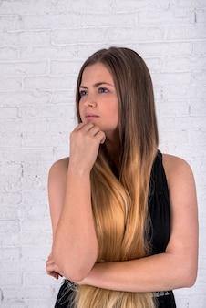 Блондинка стоит и думает на белой кирпичной стене