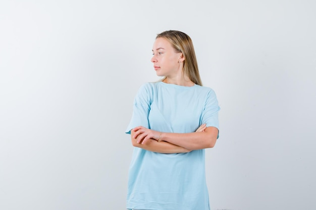 Donna bionda in piedi con le braccia incrociate, distoglie lo sguardo in maglietta blu e sembra carina