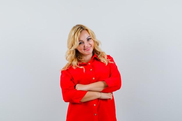 Donna bionda in piedi con le braccia incrociate in camicetta rossa e sembra carina, vista frontale.