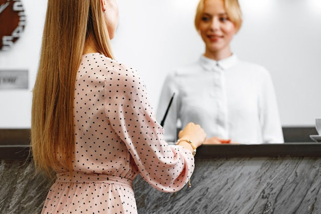 Blonde woman standing at front desk hotel reception close up