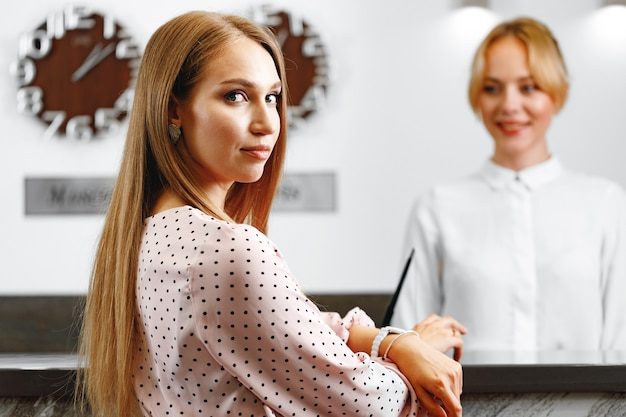 Blonde woman standing at front desk hotel reception