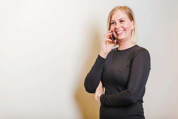 Блондинка женщина, держащая телефон, улыбаясь