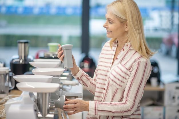 消費財のショールームに立ってミンチマシンを選ぶ金髪の女性