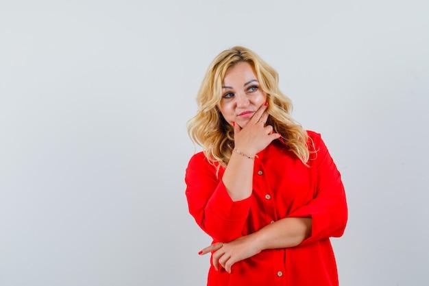 Блондинка женщина, стоя в позе мышления в красной блузке и глядя задумчиво.