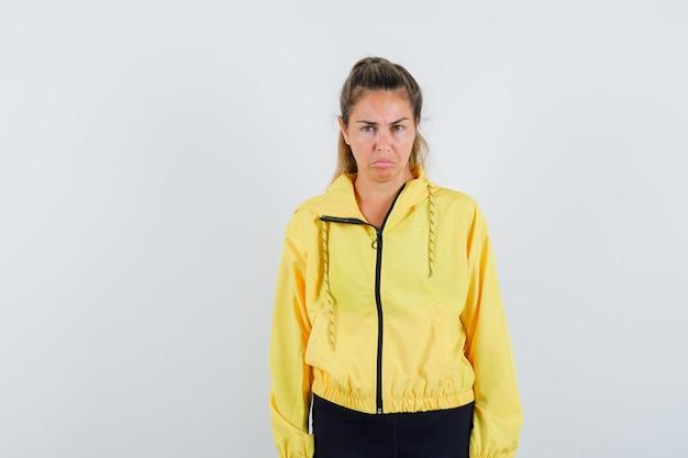 まっすぐ立って、黄色のボンバージャケットと黒のズボンで正面にポーズをとって真剣に見えるブロンドの女性