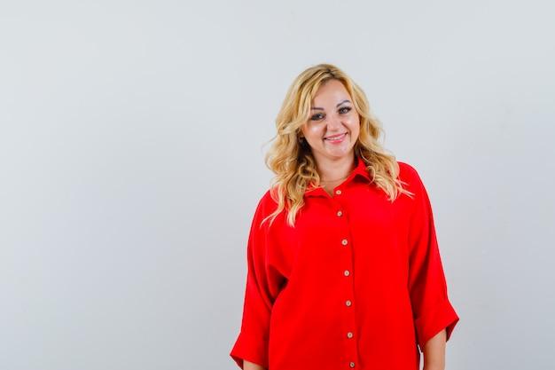 Donna bionda in piedi dritto e in posa a porte chiuse in camicetta rossa e che sembra felice