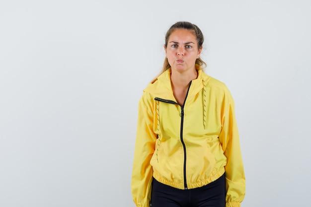 まっすぐ立って、頬を膨らませ、黄色のボンバージャケットと黒のズボンで正面にポーズをとって真剣に見えるブロンドの女性