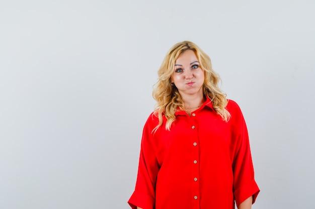 Donna bionda in piedi dritto, sbuffando guance in camicetta rossa e guardando felice
