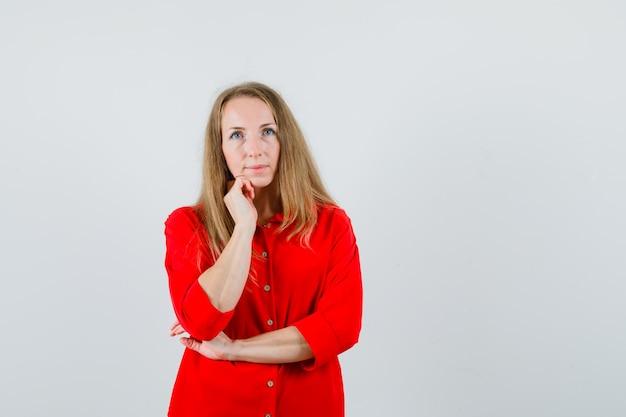 Donna bionda in piedi nel pensiero posa in camicia rossa e sembra ragionevole,
