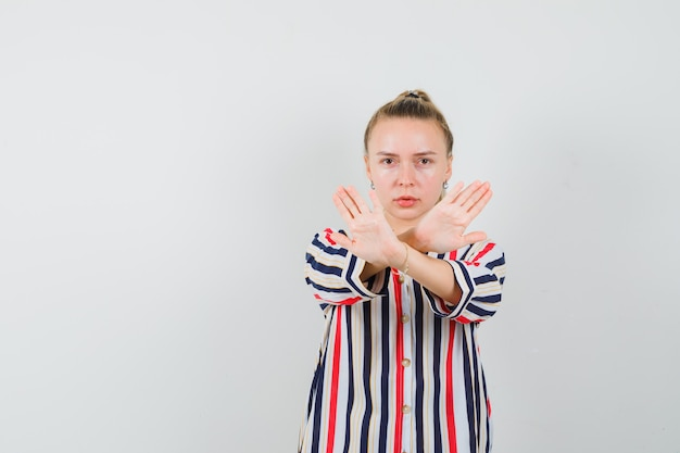 Blonde woman standing with crossed hands and showing stop gesture in striped blouse and looking serious