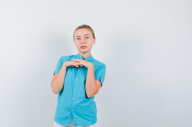 파란색 블라우스에 가슴 위에 손으로 서 있고 매력적인 고립 된 찾고 금발의 여자